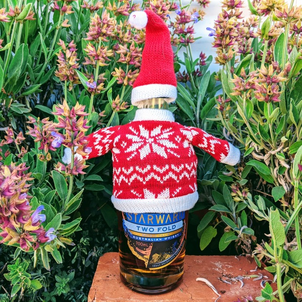 A bottle of Starward whisky wearing a christmas jumper and santa hat sitting on a red brick in a herb garden. Yes, that is a bit random I know