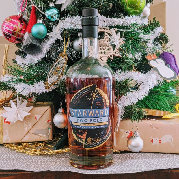 A bottle of Starward Two Fold Double Grain Australian Whisky sitting in front of a Christmas tree