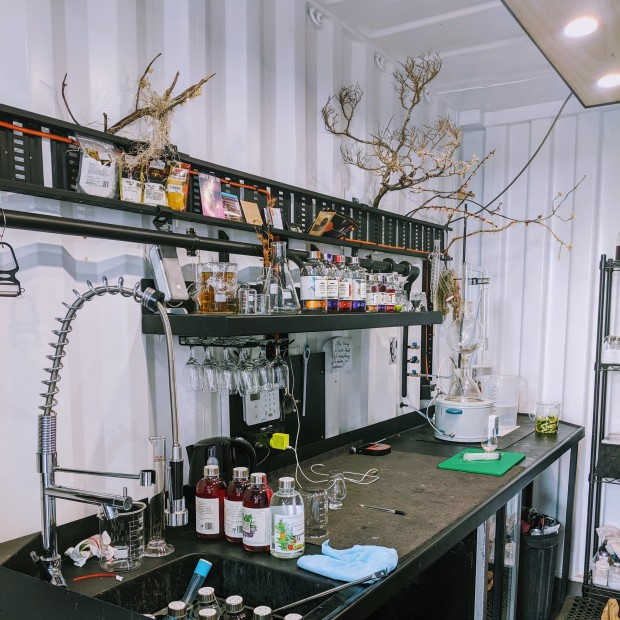 A laboratory style bench inside the shipping container that houses 7K Distillery. Clusters over brightly coloured Aqua Vitae gin bottles sit on the bench and shelving above. Dead tree branches covered in moss are artfully arranged to hang over the bench