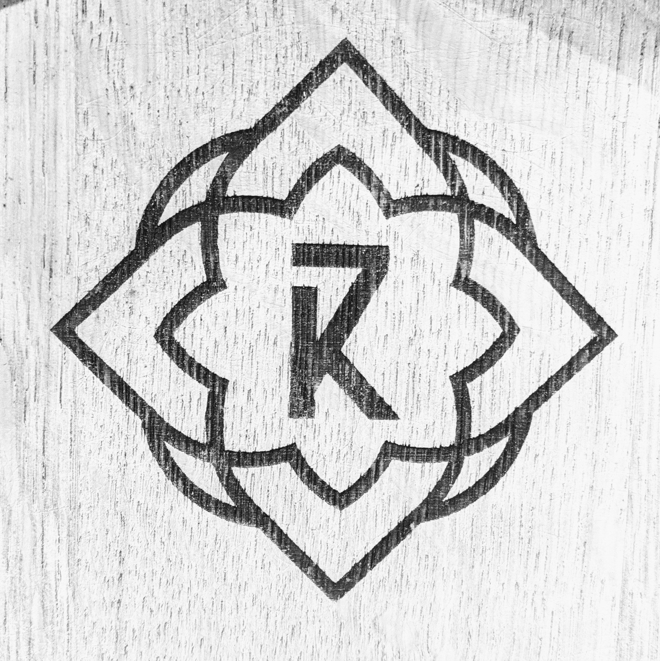 A geometric flower shape that is the logo of 7K Distillery