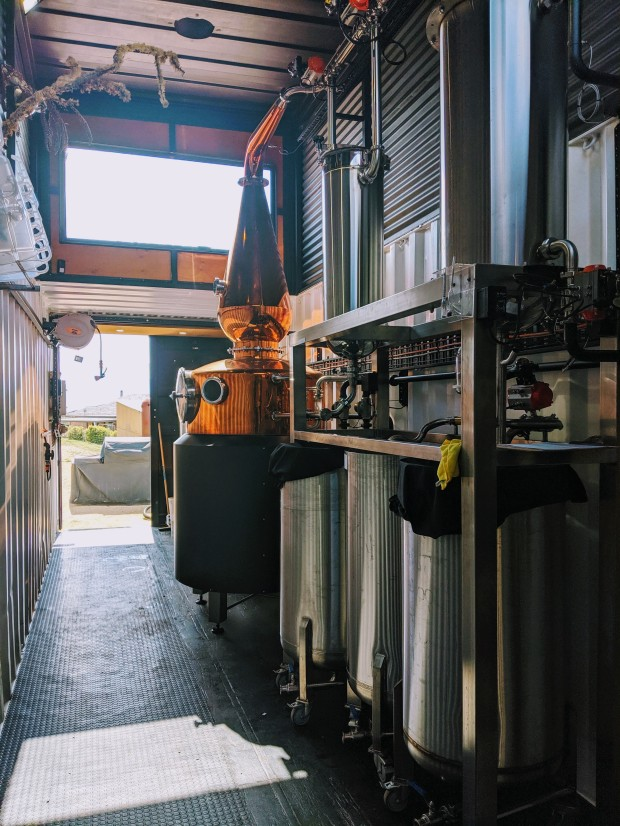 A copper still with black cladding sits next to a stainless steel gin column inside a shipping container
