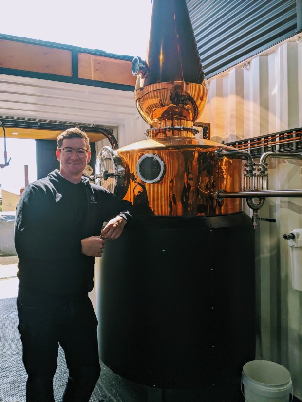 Tyler Clark of 7K Distillerty poses next to the still that he built