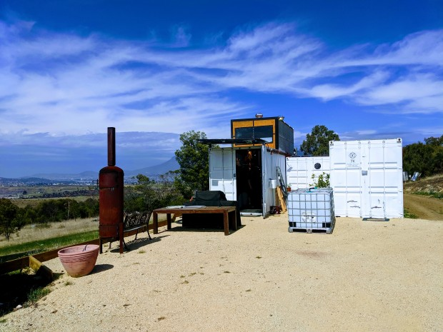 A cluster of white modified shipping containers that house 7K Distillery. The containers sit on a hill overlooking the Derwent Valley north of Hobart. Mt Wellington/kunanyi is visible in the background. There is a bright blue sky with whispy white clouds. A tall rusty fire pot sits near the containers