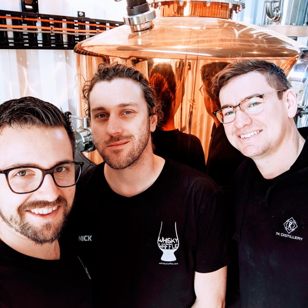 Three men standing in front of a whisky still. Two of them are Nick and Ted, world famous whisky writers from the blog Whisky Waffle. The other man is Tyler Clark, the owner of 7K Distillery